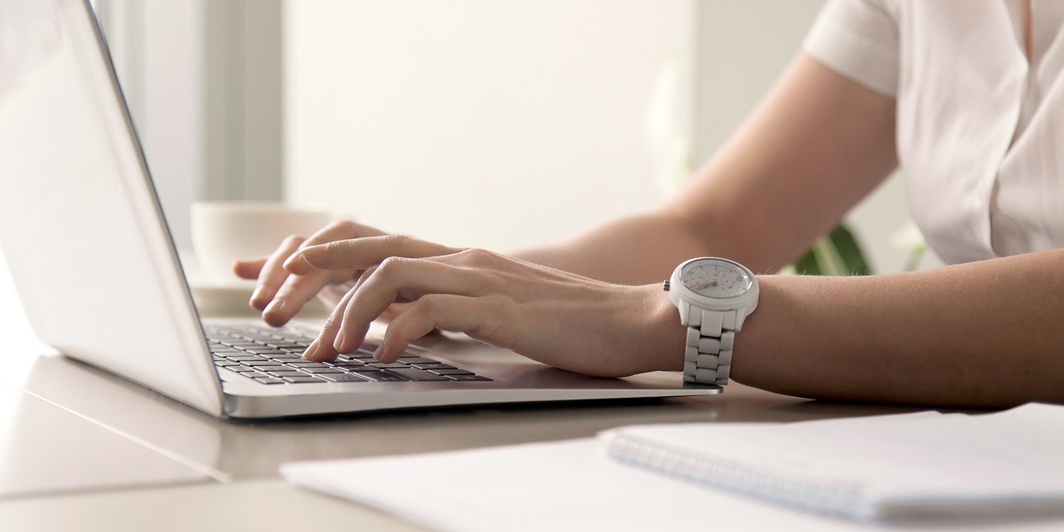 Close up image of womans hands typing on laptop at workplace. Businesswoman with white wristwatch on hand working on computer in office. Female office worker, programmer, entrepreneur searching online